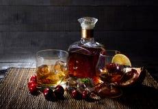 Ένα μπουκάλι του κονιάκ, ουίσκυ με δύο γυαλιά και φρούτα στο ξύλινο υπόβαθρο Στοκ Εικόνες
