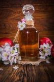 Ένα μπουκάλι του ξιδιού μηλίτη μήλων (μηλίτης), των φρέσκων μήλων και του Apple-δέντρου ανθίζει σε ένα ξύλινο υπόβαθρο Στοκ εικόνα με δικαίωμα ελεύθερης χρήσης