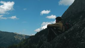 Ένα μόνο άτομο κάθεται σε έναν βράχο και εξετάζει τα βουνά φιλμ μικρού μήκους