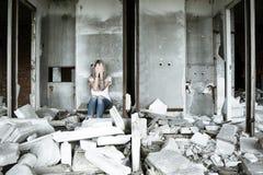 Ένα μόνο κορίτσι σε μια άσπρη μπλούζα και τα τζιν κάθεται στις καταστροφές ενός σπιτιού Λυπημένη έκφραση, τραγική ατμόσφαιρα Στοκ εικόνες με δικαίωμα ελεύθερης χρήσης