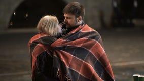 Ένα νέα αγκάλιασμα και ένα φιλί ζευγών μεταξύ τους σε ένα πάρκο πόλεων στην κρύα νύχτα φθινοπώρου φιλμ μικρού μήκους