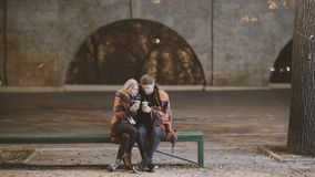 Ένα νέα αγκάλιασμα και ένα φιλί ζευγών μεταξύ τους σε ένα πάρκο πόλεων στην κρύα νύχτα φθινοπώρου απόθεμα βίντεο
