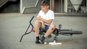 Ένα νέο αγόρι κάθεται σε ένα πάρκο μετά από να πέσει από ένα ποδήλατο, είναι ένας επικίνδυνος γύρος ποδηλάτων φιλμ μικρού μήκους