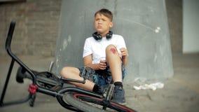 Ένα νέο αγόρι κάθεται σε ένα πάρκο μετά από να πέσει από ένα ποδήλατο, ηρεμεί τον πόνο στο γόνατό του, είναι ένας επικίνδυνος γύρ φιλμ μικρού μήκους