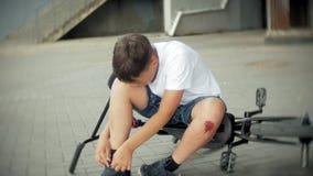 Ένα νέο αγόρι κάθεται σε ένα πάρκο μετά από να πέσει από ένα ποδήλατο, ηρεμεί τον πόνο στο γόνατό του, είναι ένας επικίνδυνος γύρ απόθεμα βίντεο