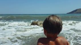 Ένα νέο αγόρι κάθεται στην παραλία στην άμμο και εξετάζει το νερό που έρχεται μέσα έξω απόθεμα βίντεο