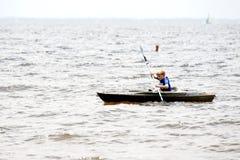 Ένα νέο αγόρι κωπηλατεί εμπρός στο νερό σε ένα καγιάκ στοκ εικόνες
