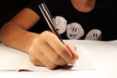 Ένα νέο αγόρι με τη μαύρη υπαγόρευση γραψίματος μπλουζών στο αγγλικό μάθημα αγοριών στοιχειώδες exellent σχολείο διαδικασίας εκμά στοκ εικόνα