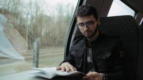 Ένα νέο αγόρι που περπατά σε ένα τραίνο, σε έναν πίνακα που διαβάζει ένα βιβλίο Αγόρι με τα γυαλιά 4K φιλμ μικρού μήκους