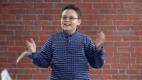 Ένα νέο αγόρι ρίχνει τα χρήματα με τα χέρια του απόθεμα βίντεο