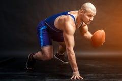 Ένα νέο αθλητικό άτομο κρατά μια καφετιά σφαίρα ράγκμπι στοκ εικόνα