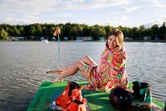Ένα νέο αθλητικό κορίτσι στην τήβεννο κάθεται στην αποβάθρα Στοκ εικόνα με δικαίωμα ελεύθερης χρήσης