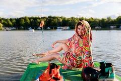 Ένα νέο αθλητικό κορίτσι στην τήβεννο κάθεται στην αποβάθρα Στοκ Φωτογραφίες