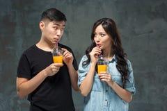 Ένα νέο αρκετά ασιατικό ζεύγος με ποτήρια του χυμού από πορτοκάλι Στοκ φωτογραφίες με δικαίωμα ελεύθερης χρήσης