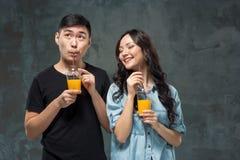 Ένα νέο αρκετά ασιατικό ζεύγος με ποτήρια του χυμού από πορτοκάλι Στοκ εικόνες με δικαίωμα ελεύθερης χρήσης