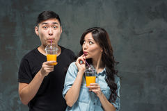Ένα νέο αρκετά ασιατικό ζεύγος με ποτήρια του χυμού από πορτοκάλι Στοκ Εικόνες