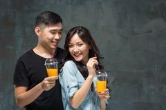 Ένα νέο αρκετά ασιατικό ζεύγος με ποτήρια του χυμού από πορτοκάλι Στοκ Φωτογραφίες