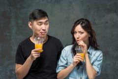Ένα νέο αρκετά ασιατικό ζεύγος με ποτήρια του χυμού από πορτοκάλι Στοκ φωτογραφία με δικαίωμα ελεύθερης χρήσης