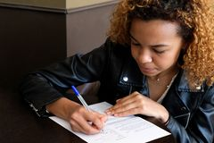 Ένα νέο αρκετά σκοτεινός-μαλλιαρό κορίτσι σε ένα μαύρο σακάκι δέρματος βάζει μια υπογραφή στο έγγραφο Η μαύρη γυναίκα υπογράφει τ στοκ φωτογραφία με δικαίωμα ελεύθερης χρήσης