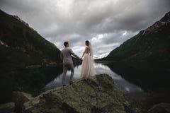 Ένα νέο γαμήλιο ζεύγος απολαμβάνει μια θέα βουνού στην ακτή μιας λίμνη στοκ εικόνες
