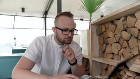 Ένα νέο, γενειοφόρο άτομο με τα γυαλιά εργάζεται στο lap-top του στο πεζούλι απόθεμα βίντεο