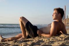 Ένα νέο ελκυστικό άτομο βρίσκεται στην άμμο κοντά στη θάλασσα και παρατηρεί τη φύση στοκ φωτογραφία
