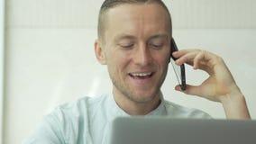 Ένα νέο επιχειρησιακό άτομο που μιλά στο τηλεφωνικό και εξέτασης ηλεκτρονικό ταχυδρομείο σε ένα lap-top απόθεμα βίντεο