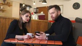 Ένα νέο εύθυμο υπόλοιπο ζευγών σε μια καφετερία και εξετάζει τις τηλεφωνικές οθόνες απόθεμα βίντεο