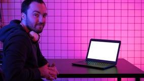 Ένα νέο εύθυμο gamer που χαμογελά στη κάμερα και που εξετάζει το lap-top Άσπρη παρουσίαση φιλμ μικρού μήκους