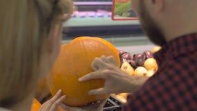 Ένα νέο ζεύγος αγοράζει μια κολοκύθα σε ένα μεγάλο κατάστημα φιλμ μικρού μήκους
