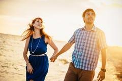 Ένα νέο ζεύγος απολαμβάνει ένα μέσο καλοκαίρι αργά το απόγευμα, σε ένα υγρό SAN στοκ εικόνα