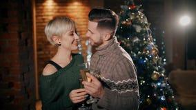Ένα νέο ζεύγος είναι ευτυχές φιλώντας το ένα το άλλο στα Χριστούγεννα, που κρατούν τα ποτήρια της σαμπάνιας απόθεμα βίντεο