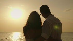 Ένα νέο ζεύγος θαυμάζει το ηλιοβασίλεμα πέρα από τη θάλασσα υποστηρίξτε την όψη απόθεμα βίντεο
