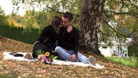 Ένα νέο ζεύγος κάθεται σε ένα άσπρο κάλυμμα στο πάρκο φθινοπώρου απόθεμα βίντεο