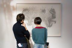 Ένα νέο ζεύγος που εξετάζει μια εικόνα Στοκ εικόνα με δικαίωμα ελεύθερης χρήσης