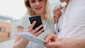 Ένα νέο ζεύγος που χρησιμοποιεί ένα κινητό τηλέφωνο υπαίθρια απόθεμα βίντεο