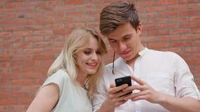 Ένα νέο ζεύγος που χρησιμοποιεί ένα κινητό τηλέφωνο υπαίθρια Στοκ εικόνες με δικαίωμα ελεύθερης χρήσης
