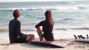 Ένα νέο ζεύγος των surfers έχει ένα υπόλοιπο στην παραλία φιλμ μικρού μήκους