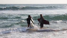 Ένα νέο ζεύγος των surfers πηγαίνει στην ωκεάνια εκμετάλλευση οι ιστιοσανίδες τους απόθεμα βίντεο