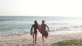 Ένα νέο ζεύγος των surfers τρέχει στον ωκεανό με τις ιστιοσανίδες φιλμ μικρού μήκους