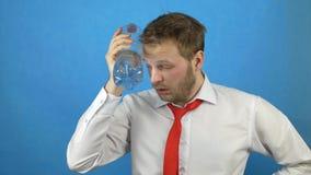 Ένα νέο καυκάσιο άτομο με μια γενειάδα και μια απόλυση εγκαθιστά ένα κρύο μπουκάλι νερό στο κεφάλι του, πονοκέφαλος, απόλυση, μπλ απόθεμα βίντεο