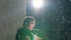 Ένα νέο καυκάσιο κορίτσι εκτελεί έναν σύγχρονο χορό χωρίς παπούτσια στο νερό κάτω από τις πτώσεις βροχής στο στούντιο χορός συναι