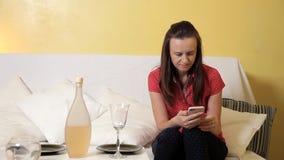 Ένα νέο κορίτσι έθεσε τον πίνακα για το γεύμα και τη συνεδρίαση στον καναπέ με το τηλέφωνο μεγάλο γεύμα παιδιών που τρώει την πίτ φιλμ μικρού μήκους