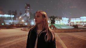 Ένα νέο κορίτσι ένα χειμερινό βράδυ στη πλατεία της πόλης Τα φω'τα των σπιτιών Το χιόνι πέφτει Κορίτσι που περιμένει το α φιλμ μικρού μήκους