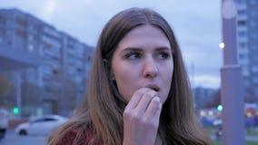 Ένα νέο κορίτσι έχει το γρήγορο φαγητό γευμάτων στη πλατεία της πόλης Νέα γυναίκα που στέκεται σε μια αστική οδό και που τρώει τα Στοκ Φωτογραφία