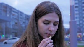 Ένα νέο κορίτσι έχει το γρήγορο φαγητό γευμάτων στη πλατεία της πόλης Νέα γυναίκα που στέκεται σε μια αστική οδό και που τρώει τα Στοκ φωτογραφίες με δικαίωμα ελεύθερης χρήσης