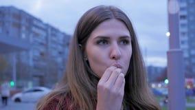 Ένα νέο κορίτσι έχει το γρήγορο φαγητό γευμάτων στη πλατεία της πόλης Νέα γυναίκα που στέκεται σε μια αστική οδό και που τρώει τα Στοκ Εικόνες