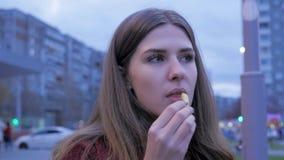 Ένα νέο κορίτσι έχει το γρήγορο φαγητό γευμάτων στη πλατεία της πόλης Νέα γυναίκα που στέκεται σε μια αστική οδό και που τρώει τα Στοκ φωτογραφία με δικαίωμα ελεύθερης χρήσης
