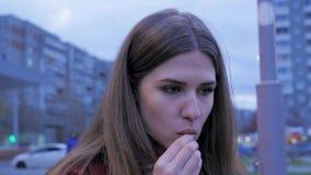 Ένα νέο κορίτσι έχει το γρήγορο φαγητό γευμάτων στη πλατεία της πόλης Νέα γυναίκα που στέκεται σε μια αστική οδό και που τρώει τα Στοκ εικόνες με δικαίωμα ελεύθερης χρήσης