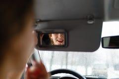 Ένα νέο κορίτσι βάζει τη σύνθεση στο αυτοκίνητο στοκ φωτογραφία με δικαίωμα ελεύθερης χρήσης